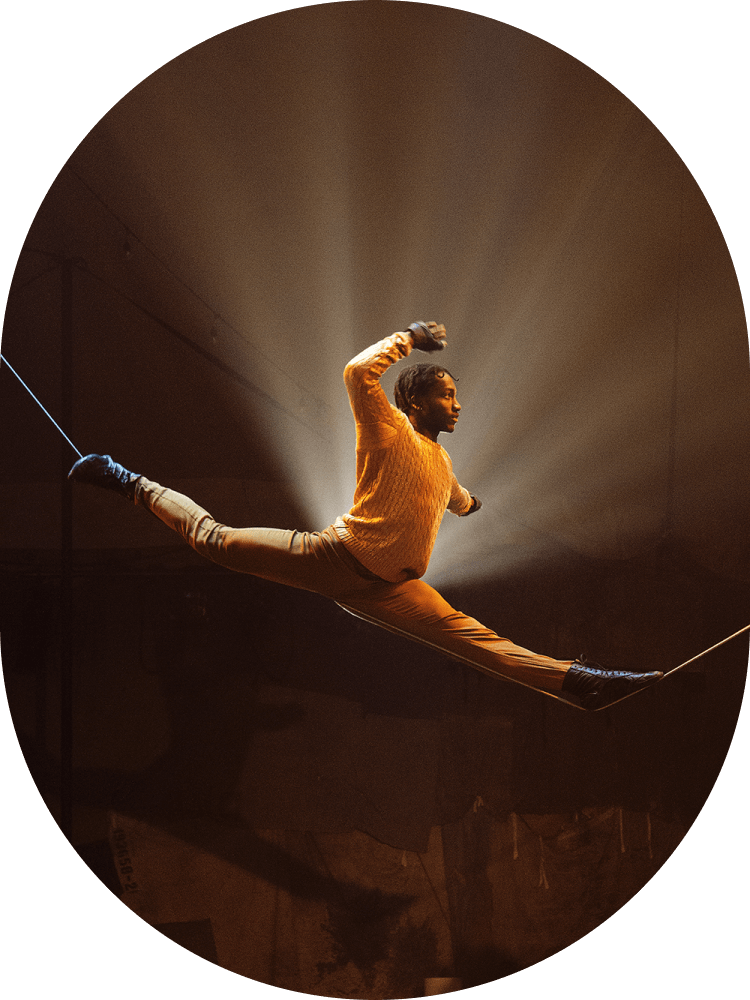 An acrobat does the splits atop a tightrope