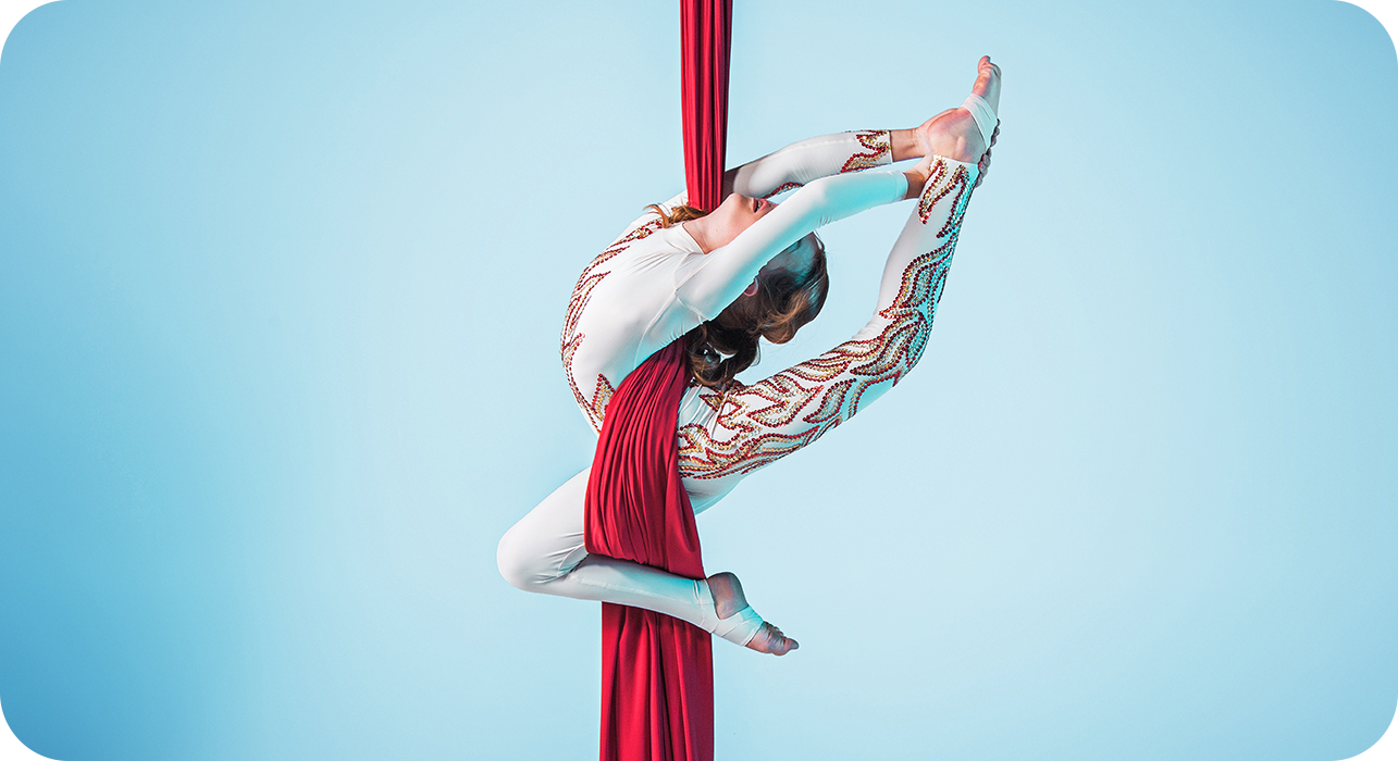 Silk Dancer holding her leg as she's suspended from the ceiling